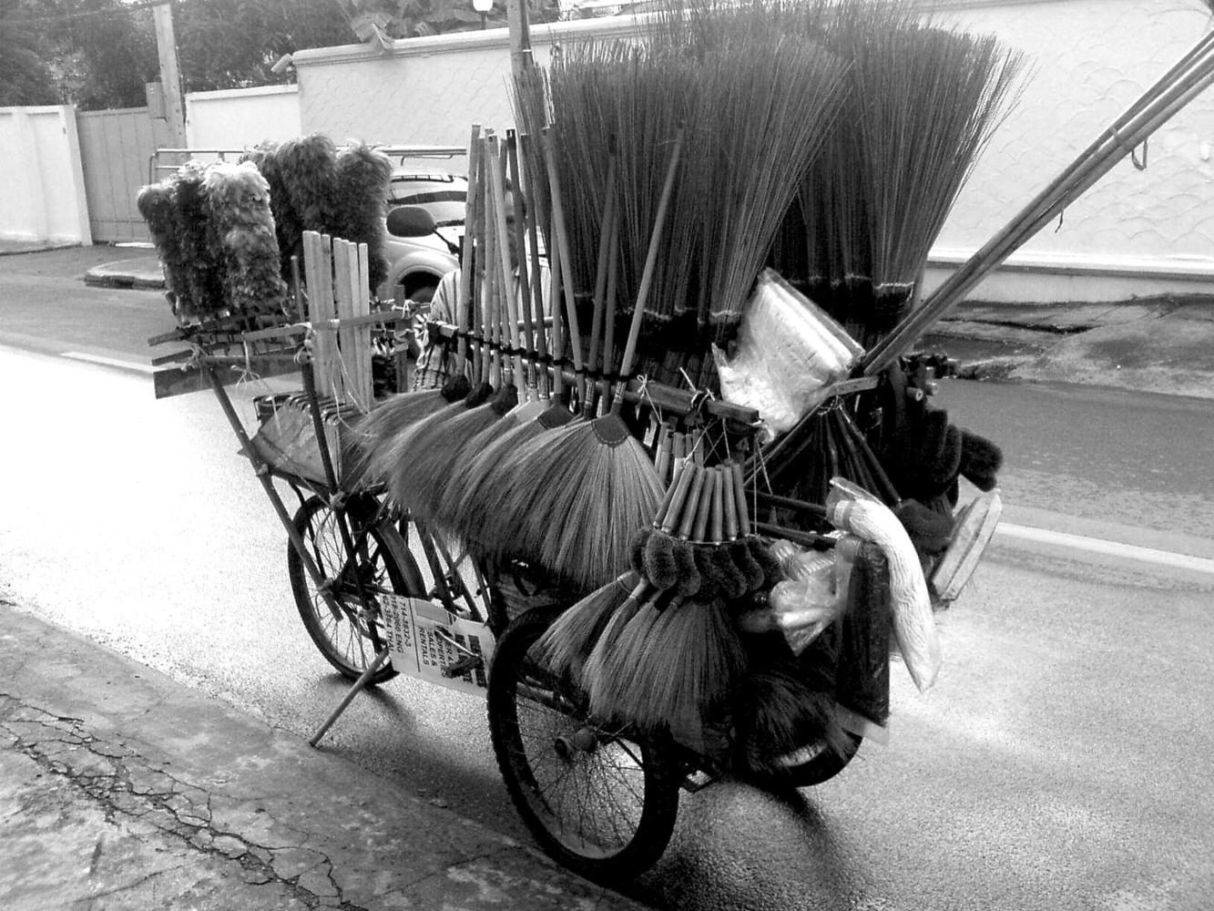 A bicycle loaded up with brooms, mops, brushes and a variety of cleaning items for sale on the streets of Thailand. Photo taken by Jett Jett Pisate Virangkabutra